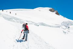 Female mountaineer ascending a glacier. Royalty Free Stock Image