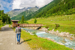 Female mountaineer by mountain stream in Alps Stock Image