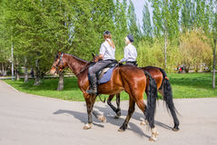 Female mounted police on horse back in the city Park Stock Photo