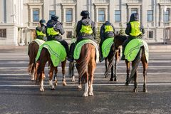 Female mounted police on horse back at the city street Stock Photo