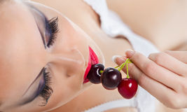 Female mouth with cherries. Young woman's mouth with red cherries Royalty Free Stock Photos