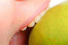 Female mouth and green apple close up Stock Photos