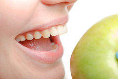 Female mouth and green apple close up Royalty Free Stock Photography