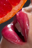 Female mouth with pummelo slice. Over dark background Stock Photos