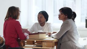 Female multiethnic company boss business woman talking to two African women at modern office table. Healthy workplace.