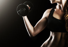Female muscular arms with dumbbells Stock Images