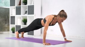 Female muscular athlete in sportswear making pushups on floor taking workout at gym