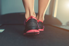 Female muscular feet in sneakers running on the treadmill at the gym. Royalty Free Stock Photos