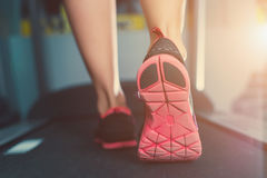 Female muscular feet in sneakers running on the treadmill at the gym. Stock Photo