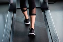 Female muscular feet in sneakers running on treadmill at gym Stock Images