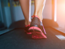 Female muscular feet in sneakers running on the treadmill at the gym. Concept for fitness, exercising and healthy lifestyle. Royalty Free Stock Image