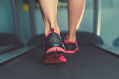 Female muscular feet in sneakers running on the treadmill at the gym. Concept for fitness, exercising and healthy lifestyle. Female muscular feet in sneakers Royalty Free Stock Images