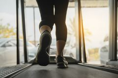 Female muscular feet in sneakers running on the treadmill at the gym, Lower body at legs part of fitness girl running on running stock photos