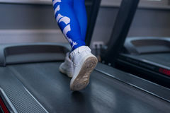 Female muscular legs on treadmill in sport gym. Concept for exercising. Fitness and healthy lifestyle Stock Photos