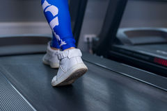 Female muscular legs on treadmill in sport gym. Concept for exercising, fitness and healthy lifestyle. Female muscular legs on treadmill in sport gym. Concept Stock Image