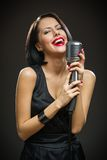 Female musician with closed eyes keeping mic Stock Photos