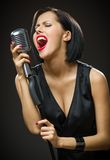 Female musician with closed eyes keeping microphone Royalty Free Stock Photo