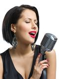 Female musician with closed eyes keeping mike Royalty Free Stock Images