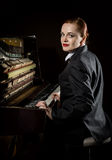 Female musician dressed in a man`s suit sitting next to the piano Royalty Free Stock Images