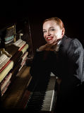 Female musician dressed in a man`s suit sitting next to the piano Stock Images