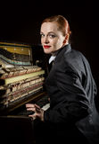 Female musician dressed in a man`s suit sitting next to the piano Royalty Free Stock Photography