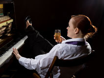 Female musician dressed in a man`s suit sitting next to the piano and drinks champagne Royalty Free Stock Image