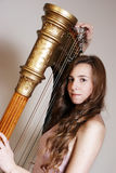 Female musician with harp Royalty Free Stock Photography