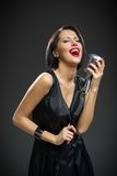 Female musician keeping mic Stock Photography