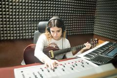 Female musician making new jingle in recording room Stock Photos