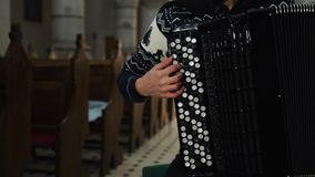 A female musician is playing the accordion in old church. Close up indoor. FHD stock video