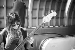 Female musician playing guitar outside subway station Royalty Free Stock Photos