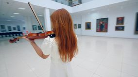 Female musician is playing the violin in the art room. 4K stock video footage