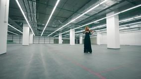 Female musician is playing the violin in an empty hall. 4K stock video footage