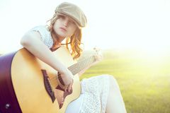 Female musician sitting on green grass playing acoustic guitar and singing songs. Talented girl relaxing at green spring or summer Royalty Free Stock Images