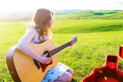 Female musician sitting on green grass playing acoustic guitar and singing songs. Talented girl relaxing at green spring or summer Royalty Free Stock Image
