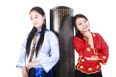 Female musicians. Two Chinese musicians with bamboo flute and zither on white Royalty Free Stock Images
