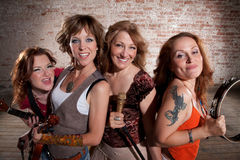Female musicians. All-girl band performing in stylish clothing at a warehouse Royalty Free Stock Photo