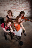 Female musicians. All-girl band performing in stylish clothing Stock Image