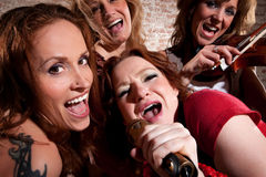 Female musicians. All-girl band performing in stylish clothing. Horizontal shot Stock Photo
