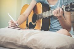 Female musicians play guitar and write songs using the tablet.This image is blurred and soft focus. stock photos