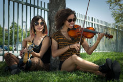 Female musicians seated under a tree playing instruments Stock Photos