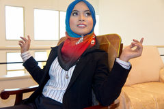 Female Muslim businesswoman. Attractive Muslim businesswoman in chair with traditional hijab Stock Image