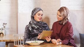 Female muslim college students using tablet computer in cafe. Female muslim college students using tablet computer in cafe stock video footage