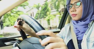Female muslim driving a car. On the street while wearing glasses and a veil, shot in 4k resolution stock video footage
