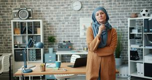 Female Muslim office worker in hijab standing in workplace holding glasses. Looking at camera with serious face. Attractive people, lifestyle and work concept stock video footage