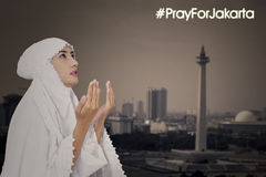 Female muslim praying for Jakarta Stock Image