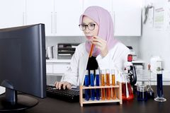 Female scientist works in the lab. Female muslim scientist works in the lab while holding a test tube and using a computer Stock Photography