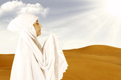 Female muslim in white praying at desert Stock Image