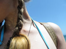 Female naked neck, shoulder and hair in a pigtail close-up against a blue sky. A girl in a swimsuit resting on the sea - concept, abstract Royalty Free Stock Image