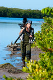 Female nature photographer. Professional female nature photographer in waders coming out of the water Stock Photo